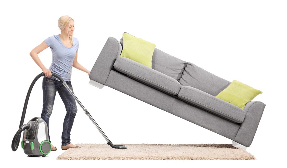 Woman Picking Up Couch And Vacuuming Under With Top Selling Canister Vacuum